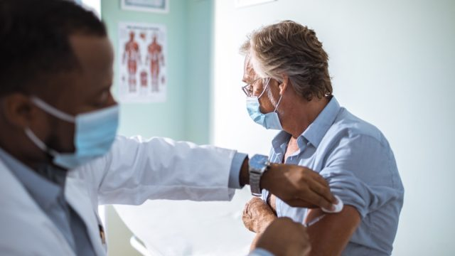 Close up of a mature man taking a vaccine in his doctors office