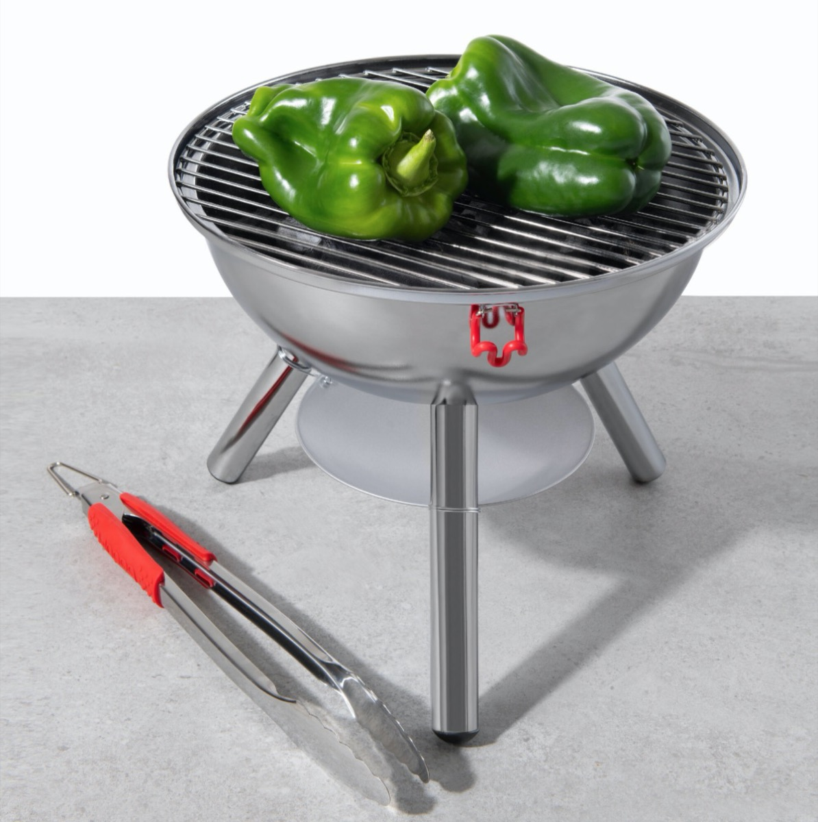 small silver grill with green pepper on it next to tongs