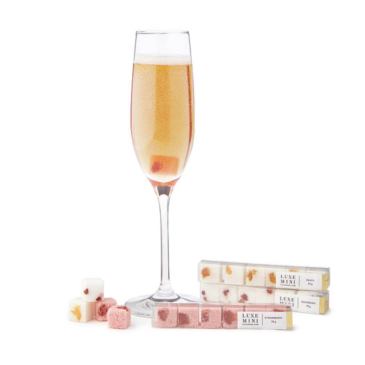 champagne glass next to pink sugar cubes