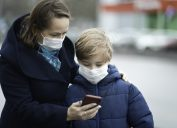A mother wearing a face mask shows her son something on her smartphone while he also wears a mask.