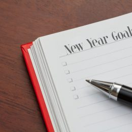 """red journal open to whit lined page with """"new years goals"""" written in top left corner and pen sitting atop paper"""