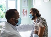 doctor in surgical mask giving male patient in mask a vaccine in arm