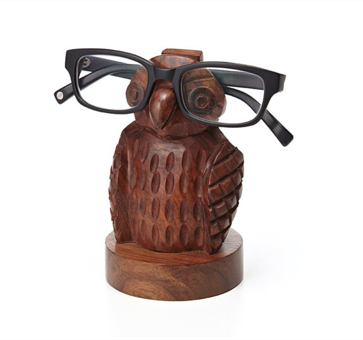 small wooden owel with black human eyeglasses on it