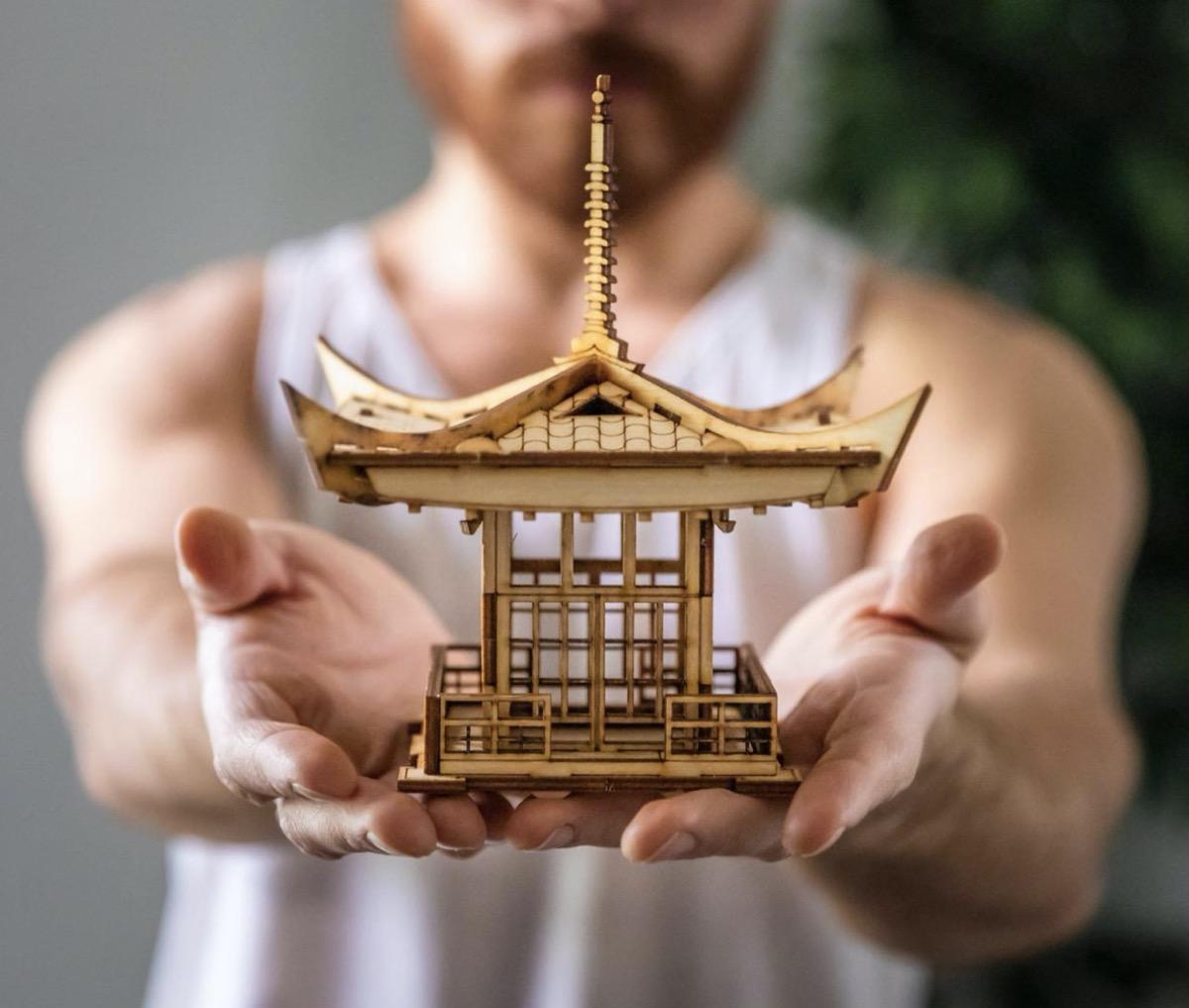 man holding tiny wooden pagoda