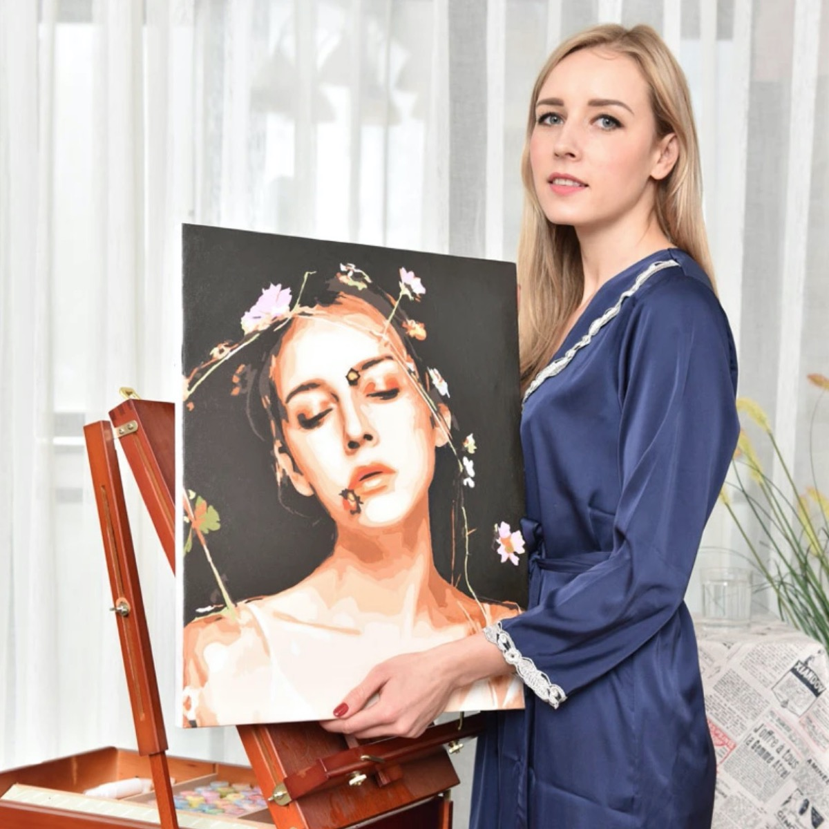 young blonde woman in blue robe holding painting of herself