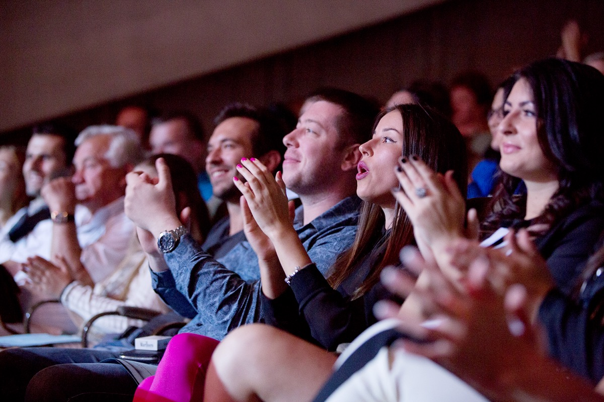 People applauding as they're watching a concert