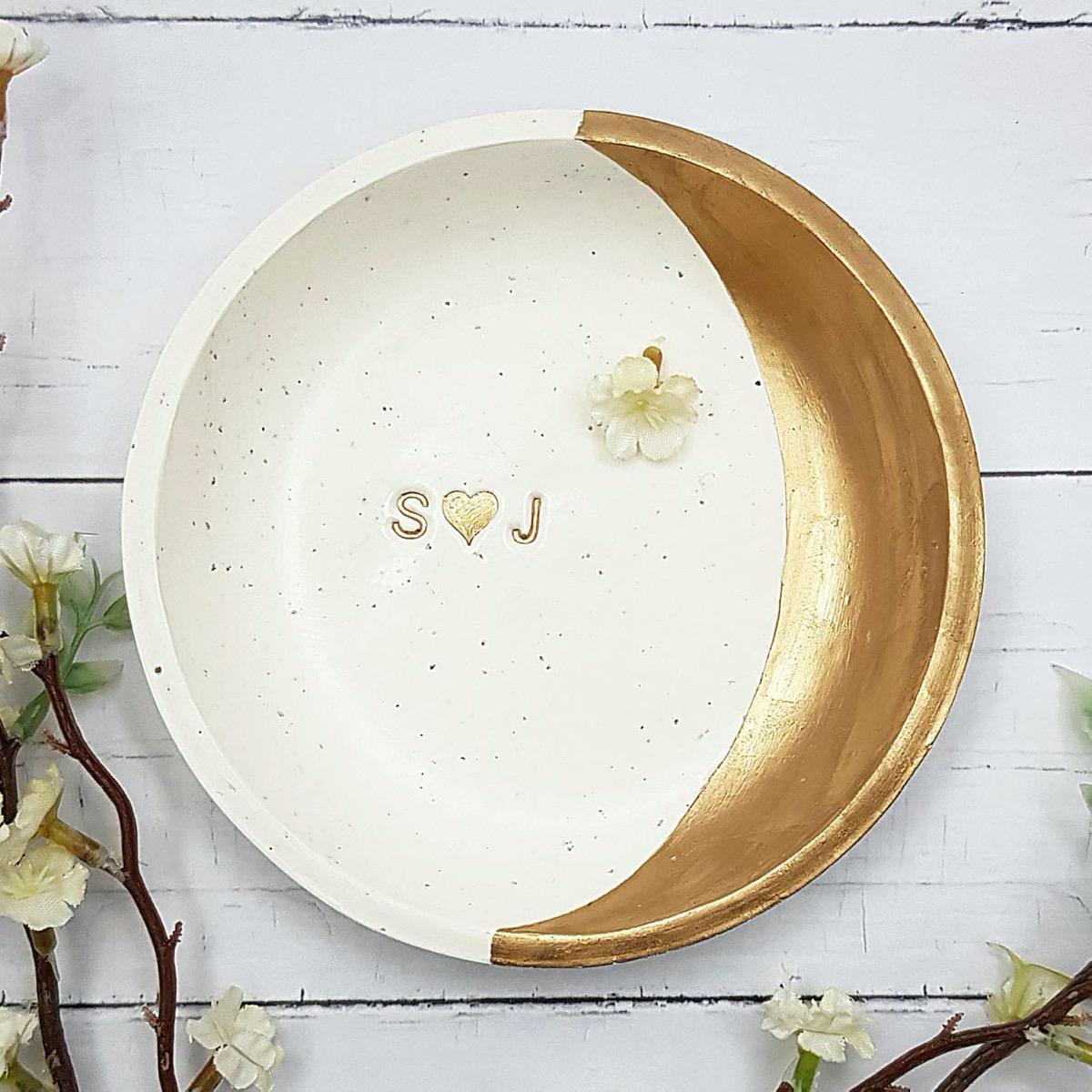 white jewelry dish with gold half moon shape on one side