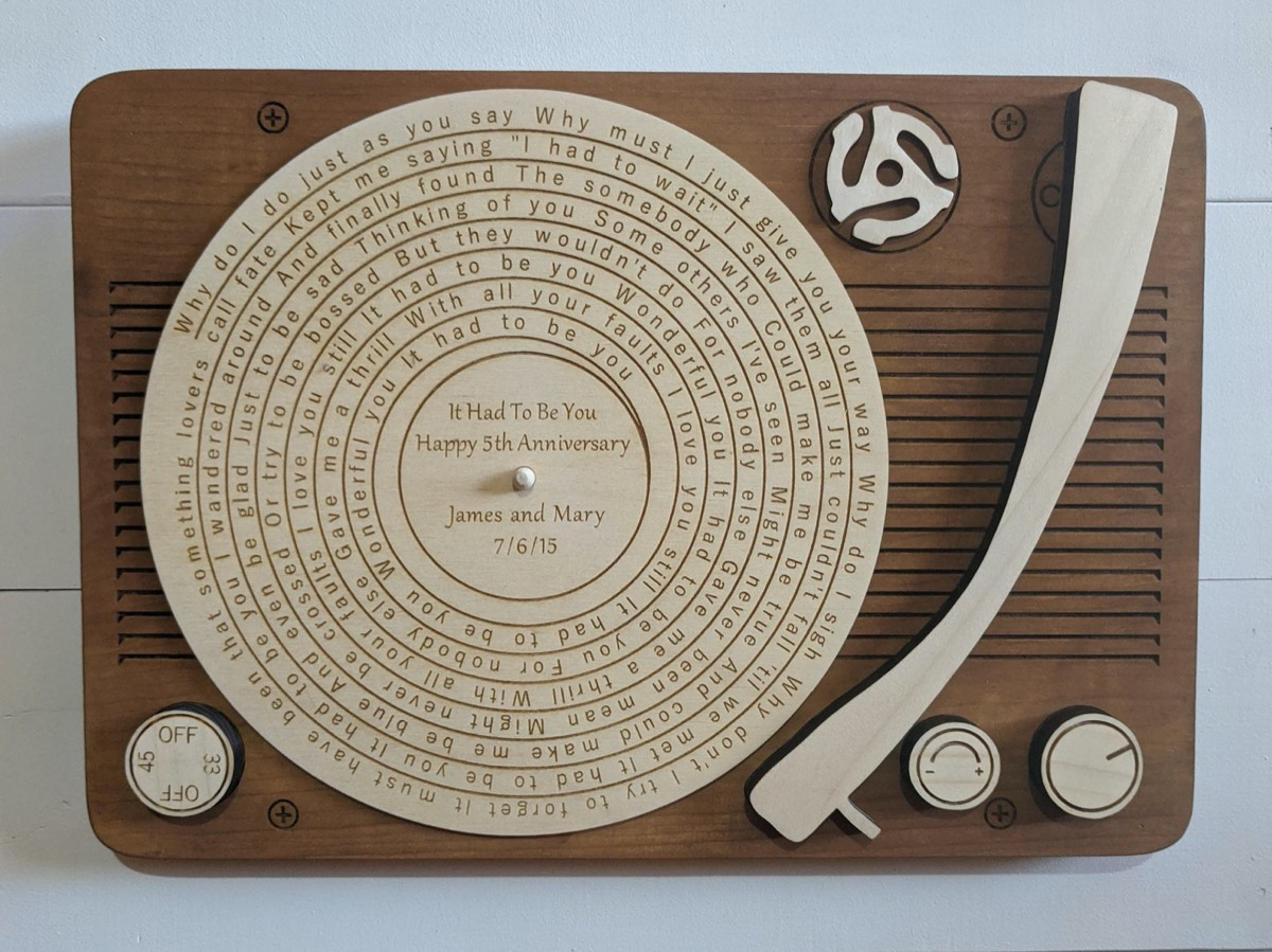 wooden record player engraved with song lyrics