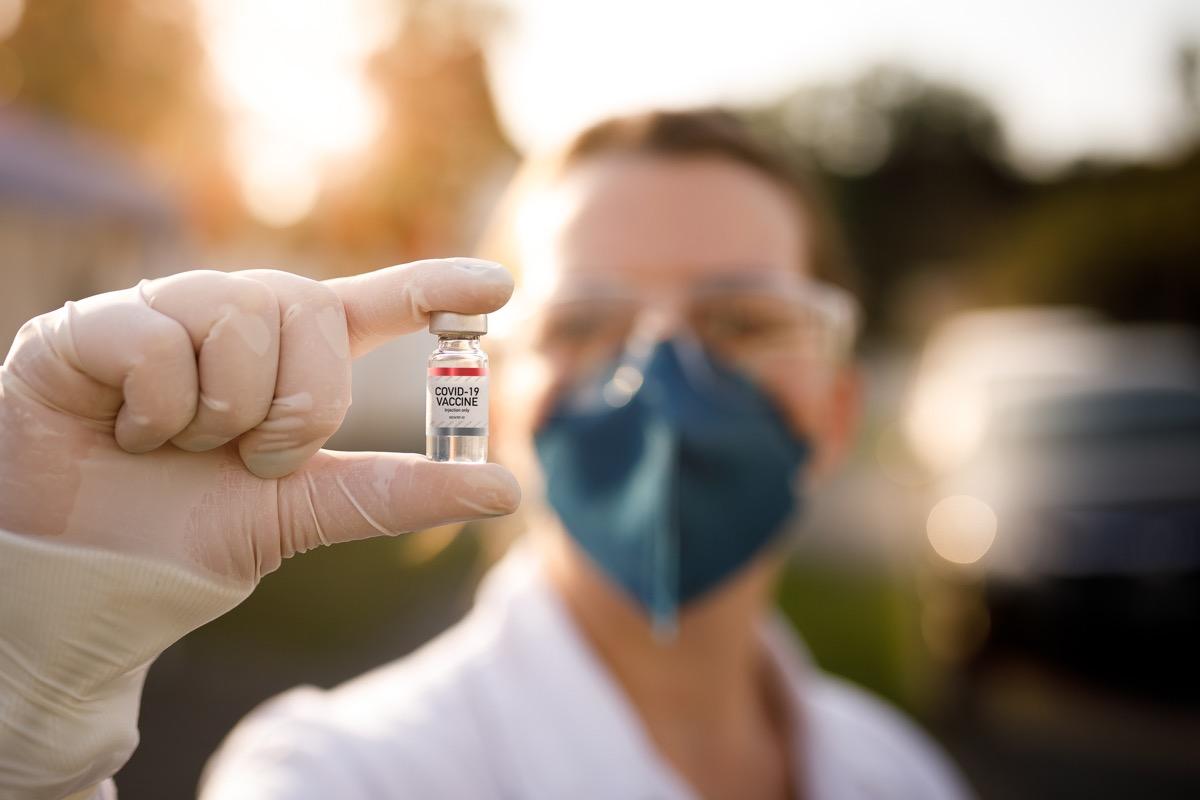 Woman holding covid-19 vaccine.