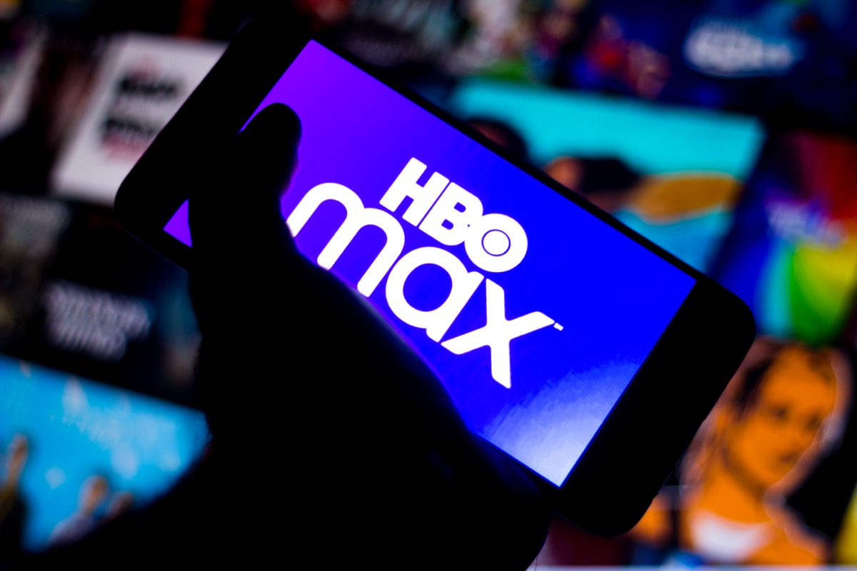 a phone in someone's hand that says HBO Max on the screen