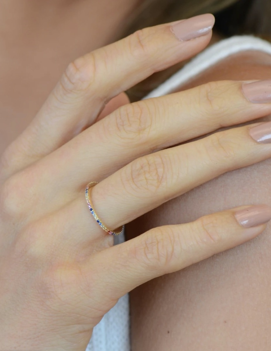 woman's hand with rainbow eternity band on it