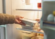 Man's hand taking wrapped up food out of refrigerator.