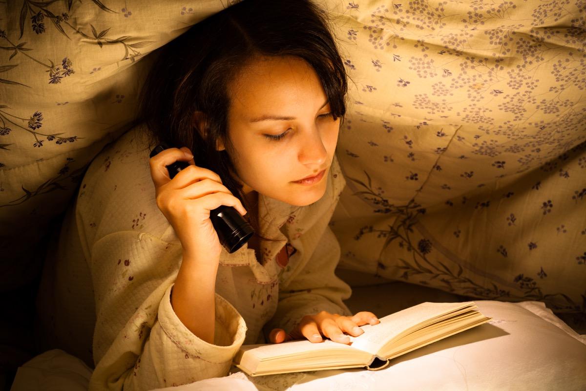 Woman reading by flashlight