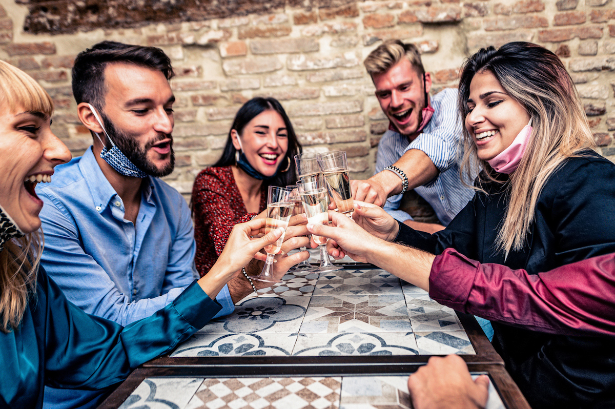 Young people with face masks on chins toasting with champagne flutes amid coronavirus