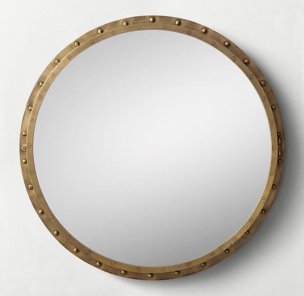 round gold mirror on white wall