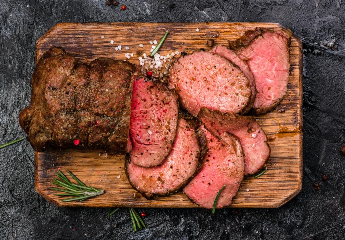 sliced roast beef on a wooden cutting board