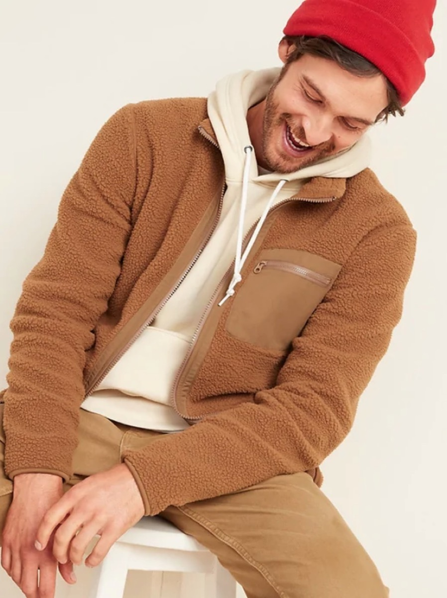 young man in red hat and brown fuzzy jacket
