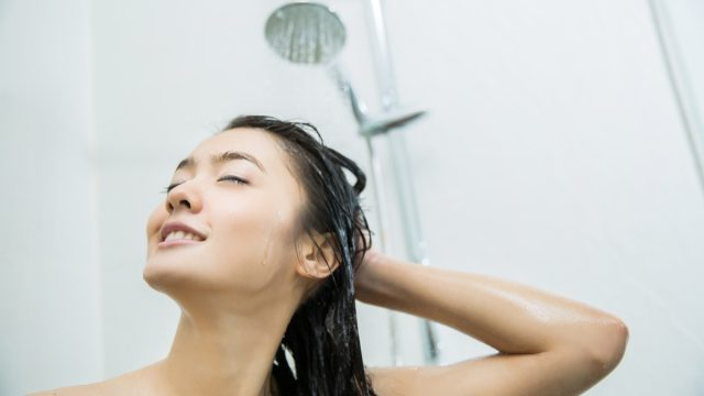 woman smiling while taking shower