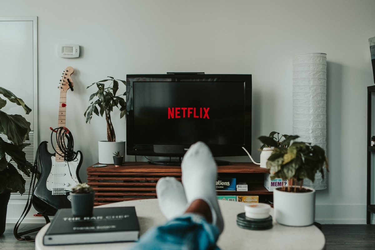 man's feet on the table while netflix is on the tv in front of him