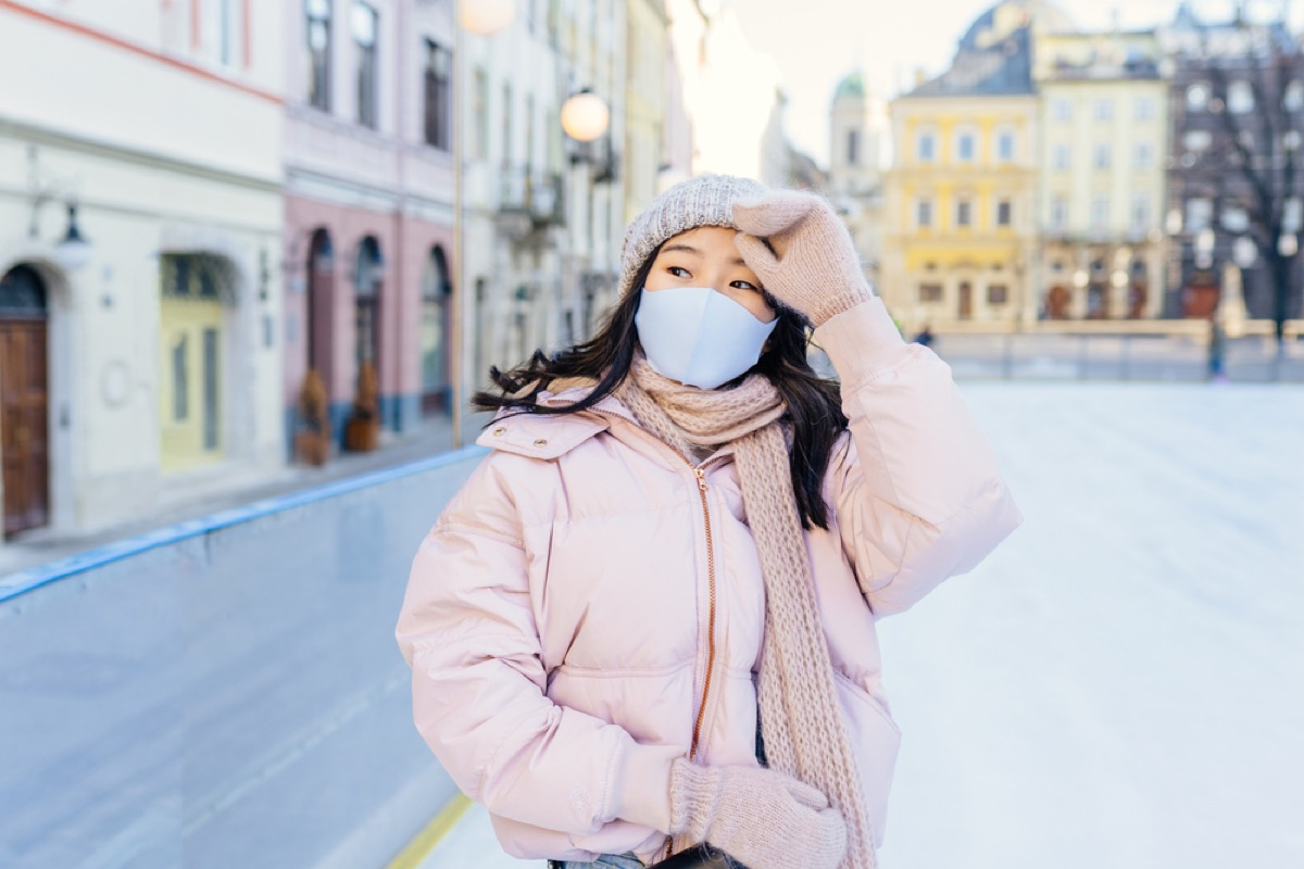 woman in winter clothing with face mask on ice skating rink