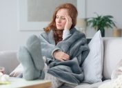 Sick woman on couch with headache and fever