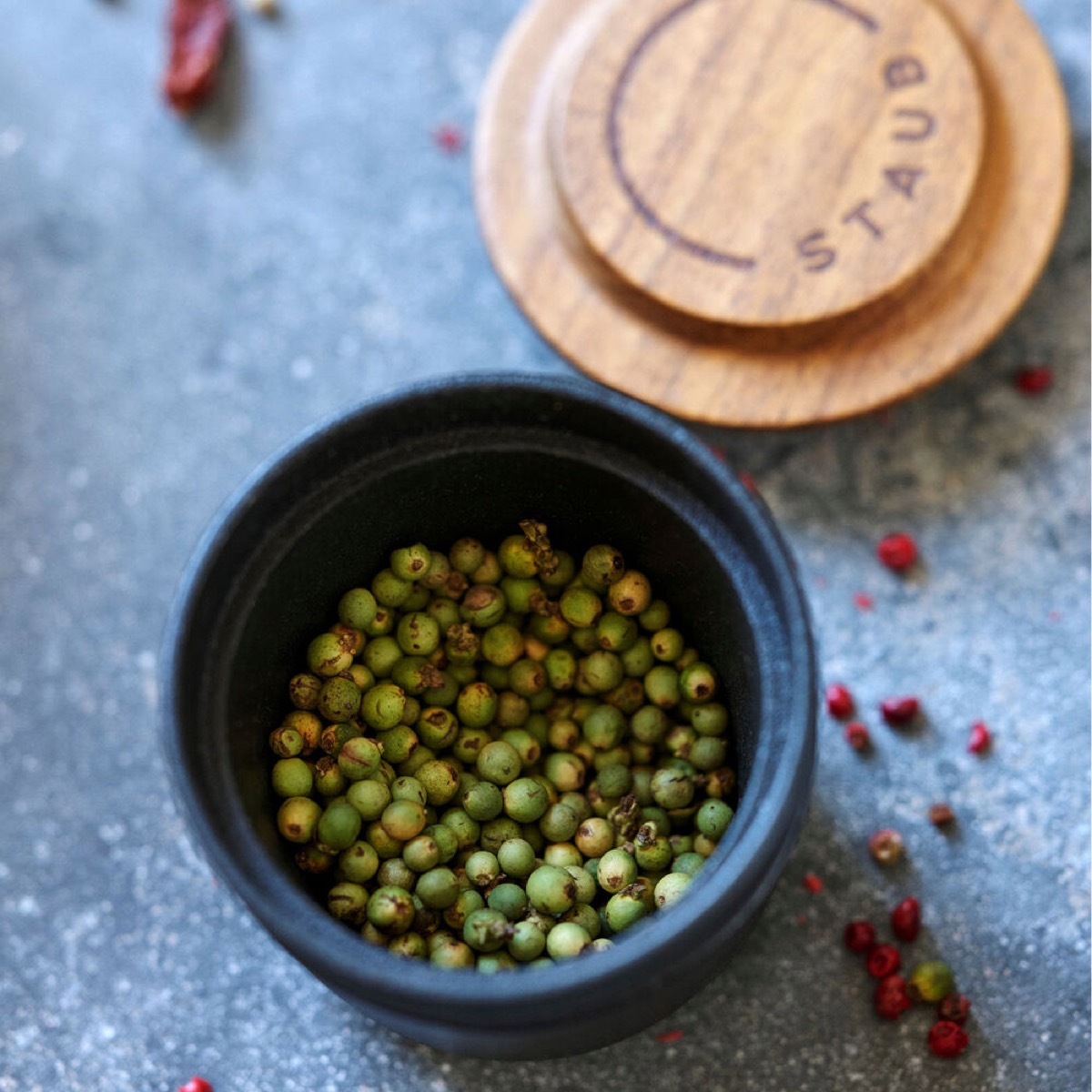 green peppercorns in spice grinder