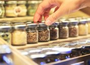closeup woman's hand picking jar of spices