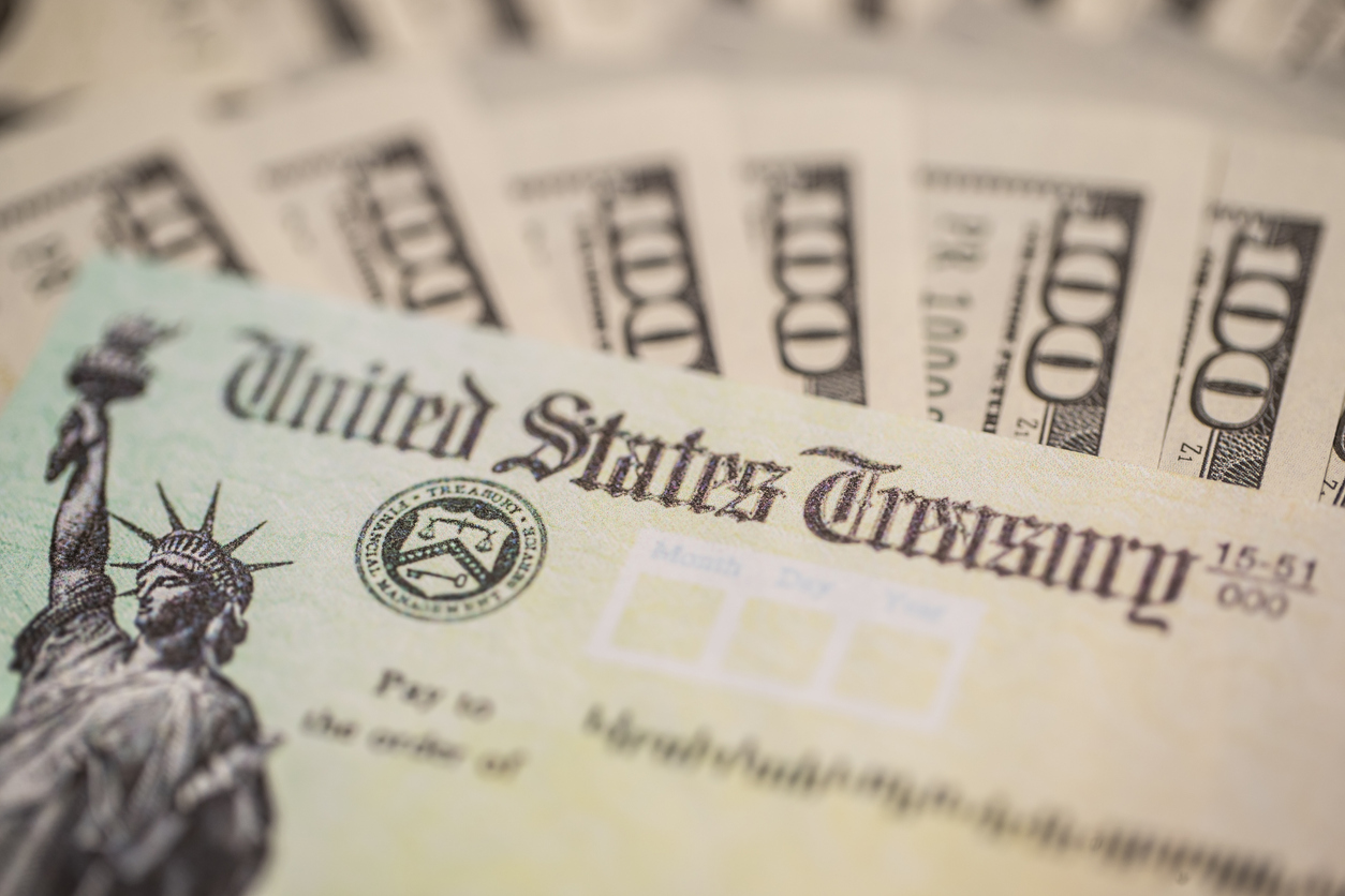 A federal stimulus check sitting on top of $100 bills