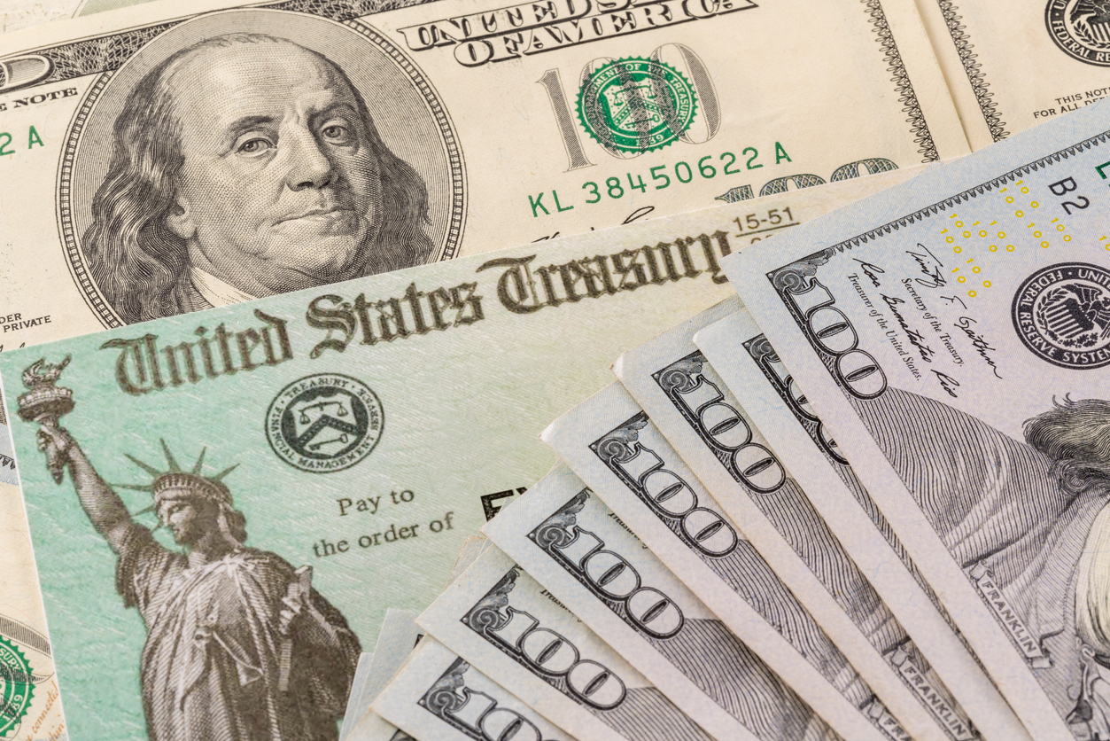 A COVID-19 stimulus check sits in between $100 bills