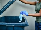 A young woman wearing protective gloves throwing away a face mask into a garbage can.