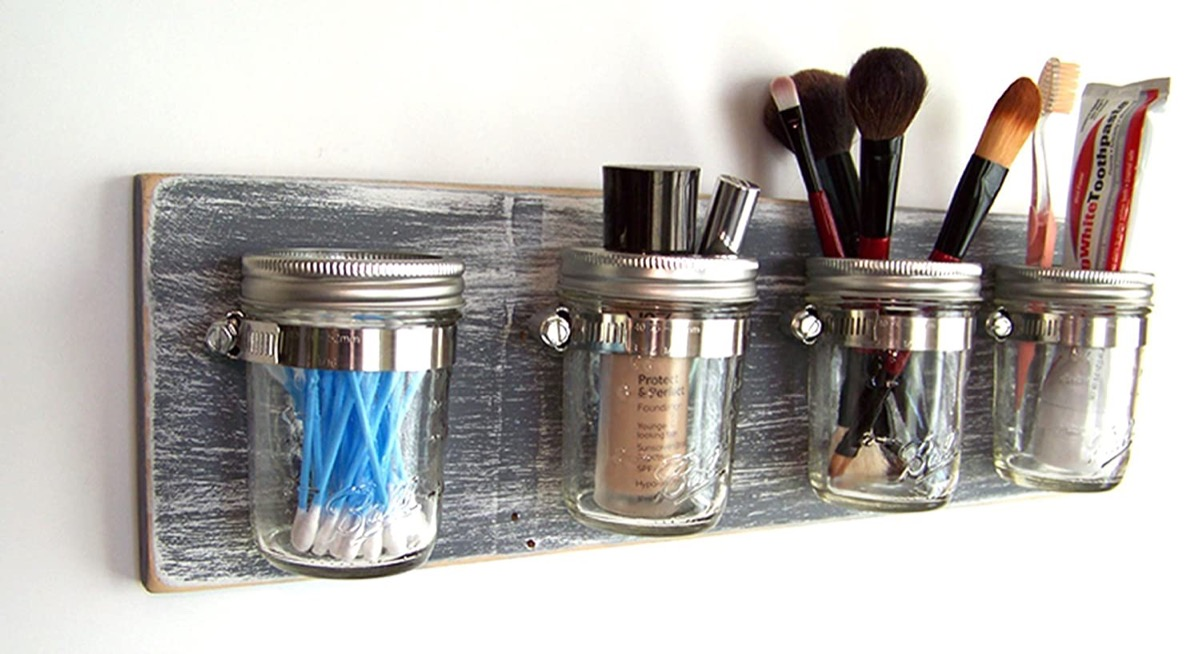 mason jars full of toiletry products and makeup on wooden board
