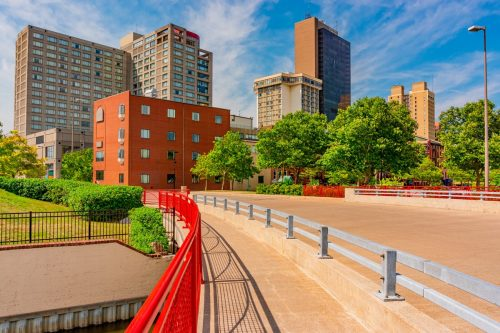 bridge with a bright red railing and buildings in downtown Toledo, Ohio