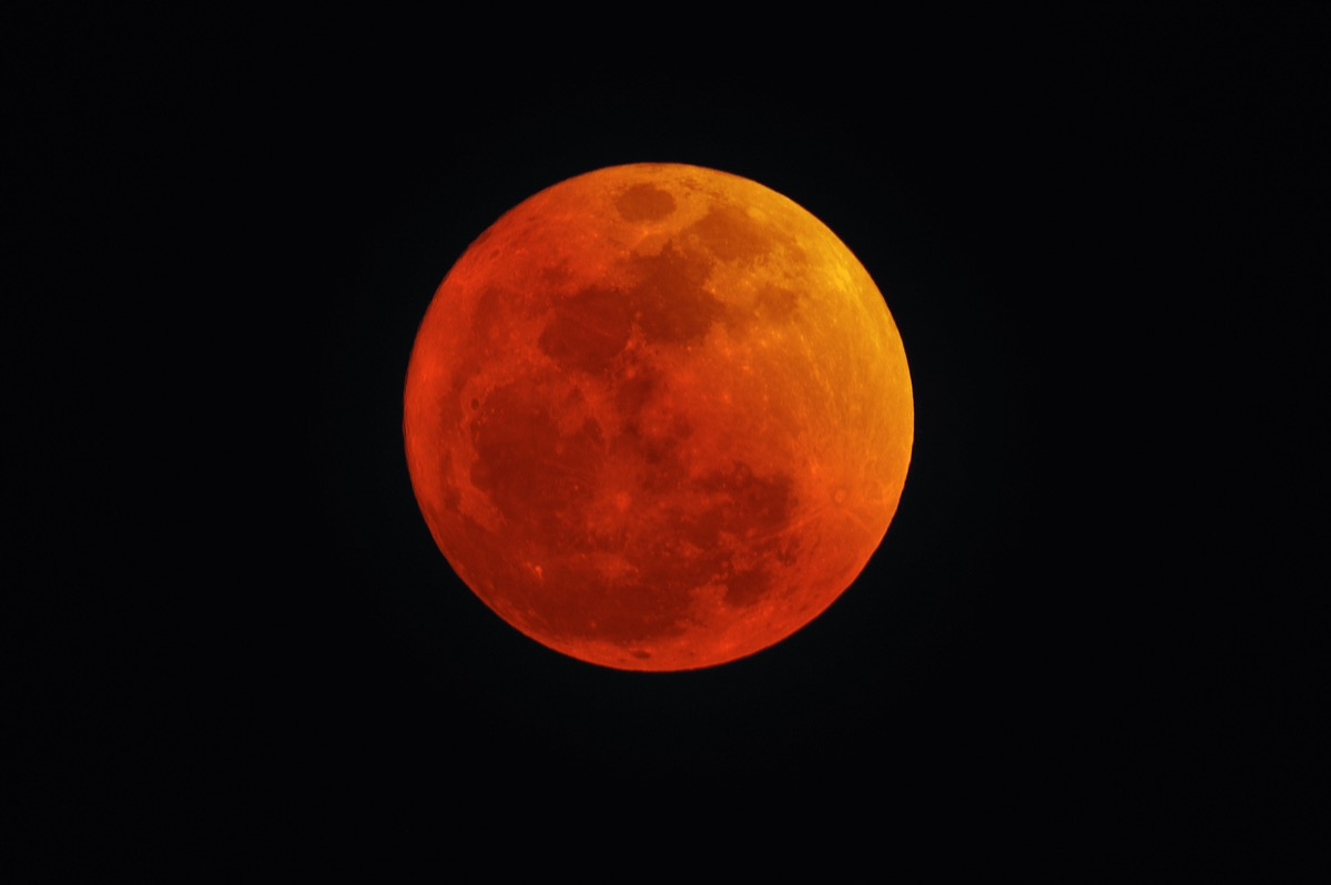 A red and orange moon in the dark night sky