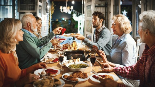 Closeup of multi generation family having Thanksgiving dinner. There are two senior couple and a mid 20's couple having a big feast, sharing food and love.
