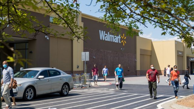Kennesaw, GA / USA - 04/05/20: Walmart line outside the store with masked people practicing social distancing 6 feet apart during Covid-19 Corona Virus Pandemic.