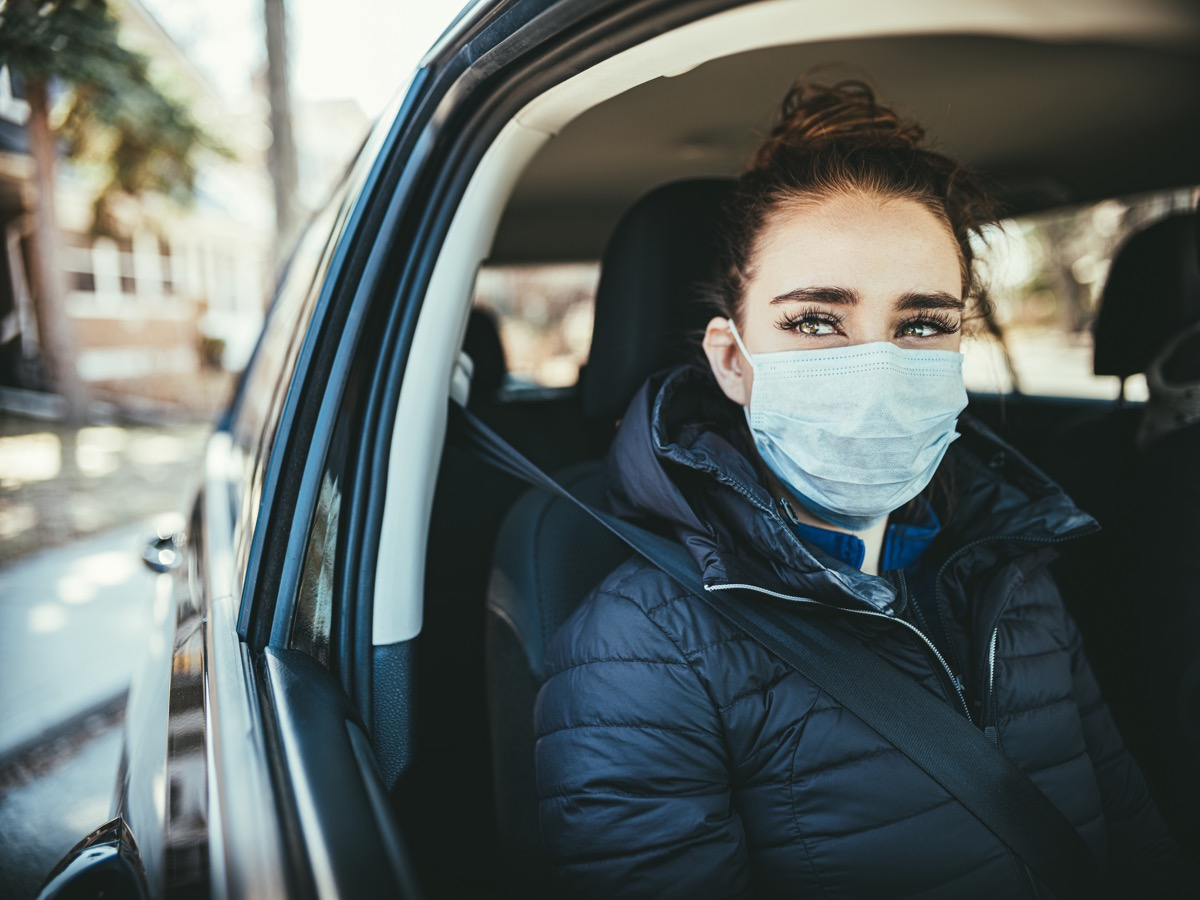 Young woman wearing disposable face mask while riding in car. Mask is Disposable Earloop Face Mask with Filters against Bacteria.