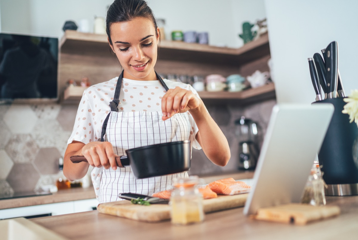 Young woman using digital tablet while cooking salmon filet in kitchen