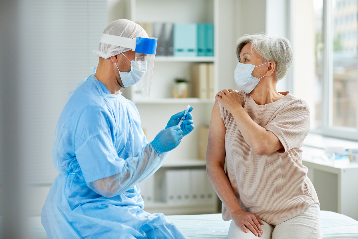 An older woman pulling up her sleeve to get a COVID vaccine from a male health care worker wearing PPE.