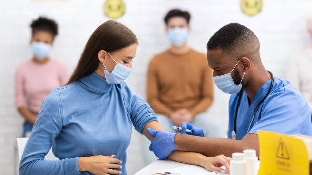 woman in surgical mask getting covid vaccine from medical professional in blue scrubs and surgical mask