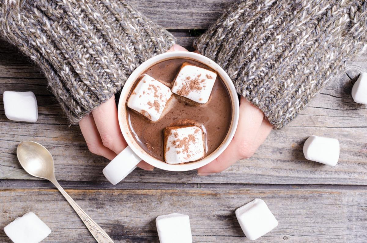person wearing gray sweater holding mug of hot chocolate