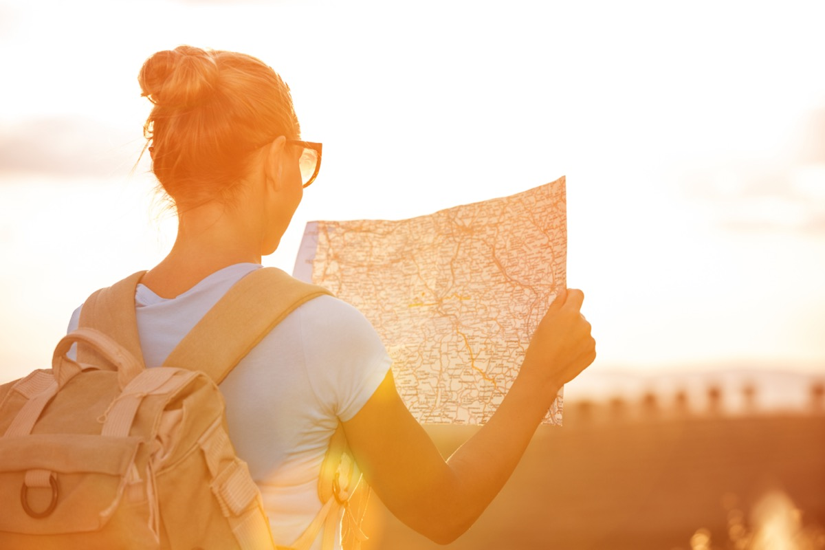 woman wearing a backpack and holding a map