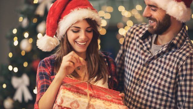 man giving woman gift and they're both wearing santa hats