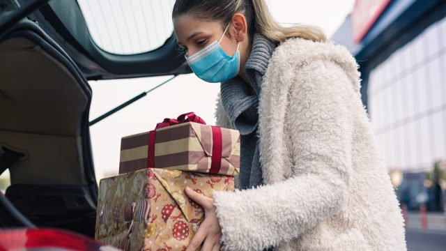A young woman wearing a face mask place a stack of holiday presents into the trunk of a car..
