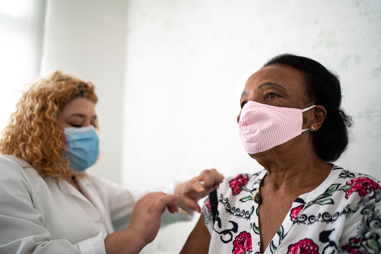 A senior woman wearing a face mask receives a COVID-19 vaccine from a female healthcare worker.