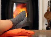 woman in gray socks with feet in front of space heater