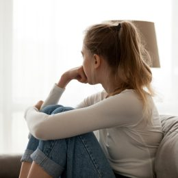 Woman sitting on couch in deep thought