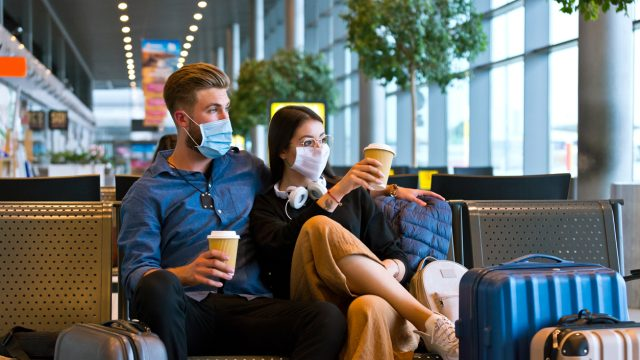 A young couple wearing face masks while sitting in a transit lounge waiting to travel during the holidays.