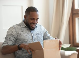 young man looking excited while opening cardboard box