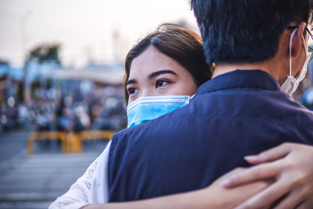 Young millennials hugging and wearing a protective face mask