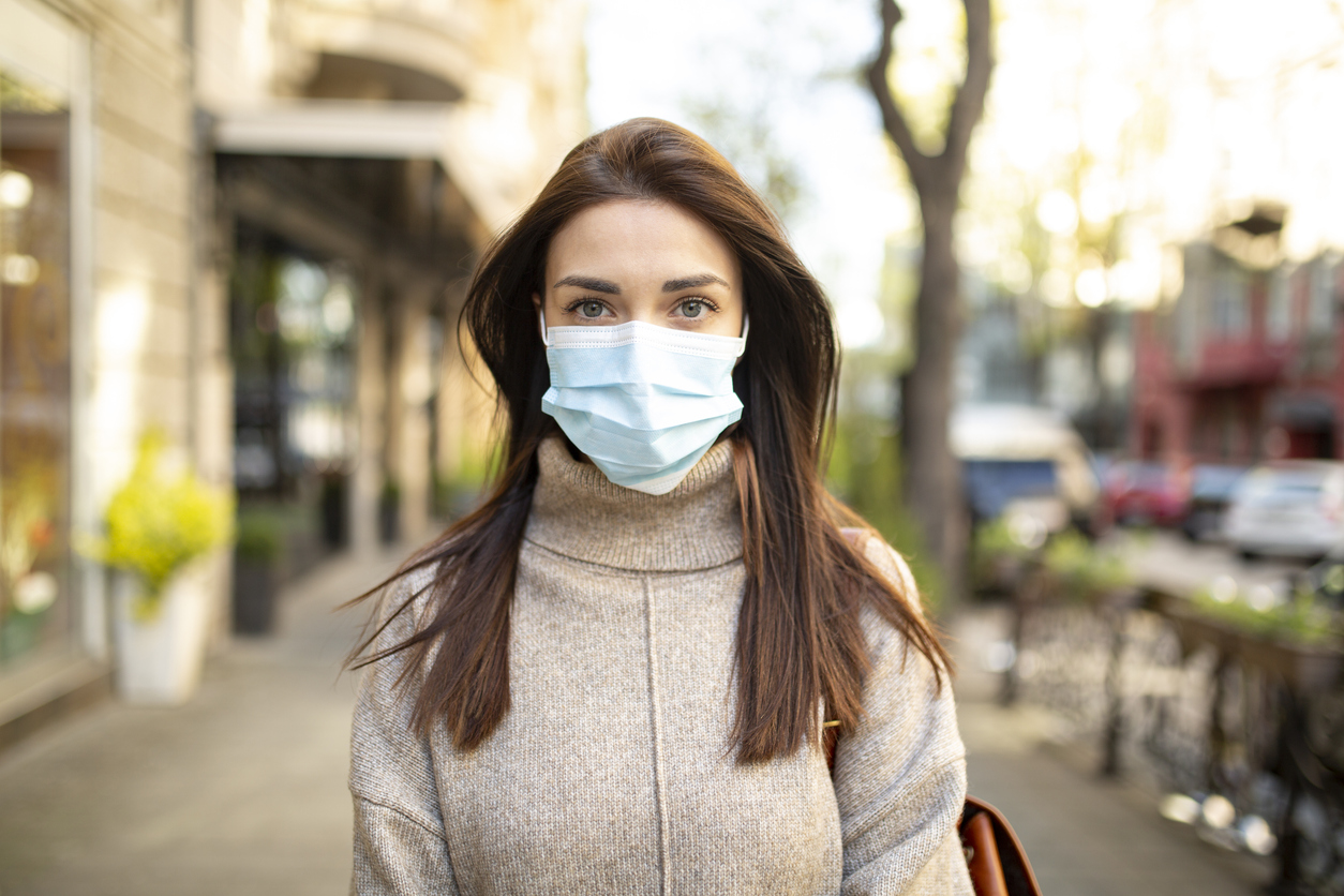 A young woman wearing a face mask in public to protect herself from COVID-19